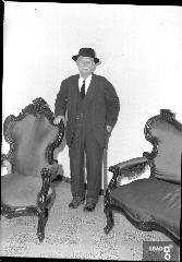 Uomo anziano con bastone accanto a una poltrona. [Gabriele Sansone. Su indicazione di Antonino Gallotta]