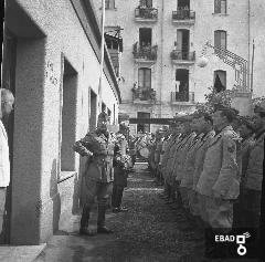 Passaggio di autorità militari davanti ad una parata di militari. [La foto è stata scattata nel 1940-1943 a SALERNO negli spazi di VIA BASTIONI dell'ex MONASTERO di SAN MICHELE ARCANGELO, di età longobarda e soppresso nel 1866; negli anni a cui risale la foto, una parte dell'ex Monastero era adibita a CASERMA della MILIZIA VOLONTARIA PER LA SICUREZZA NAZIONALE, indicata più semplicemente con l'acronimo MVSN, ma anche identificata con l'espressione CAMICIE NERE. In particolare la foto si riferisce alla visita in Caserma di un Console della MVSN. Su indicazione di Massimo La Rocca]