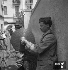 Musicista che suona. [La foto è stata scattata nel 1940-1943 a SALERNO negli spazi di VIA BASTIONI dell'ex MONASTERO di SAN MICHELE ARCANGELO, di età longobarda e soppresso nel 1866; negli anni a cui risale la foto, una parte dell'ex Monastero era adibita a CASERMA della MILIZIA VOLONTARIA PER LA SICUREZZA NAZIONALE, indicata più semplicemente con l'acronimo MVSN, ma anche identificata con l'espressione CAMICIE NERE. In particolare la foto si riferisce alla visita in Caserma di un Console della MVSN. Su indicazione di Massimo La Rocca]