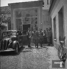 Autorità militare e macchina d'epoca. La foto è stata scattata nel 1940-1943 a SALERNO negli spazi di VIA BASTIONI dell'ex MONASTERO di SAN MICHELE ARCANGELO, di età longobarda e soppresso nel 1866; negli anni a cui risale la foto, una parte dell'ex Monastero era adibita a CASERMA della MILIZIA VOLONTARIA PER LA SICUREZZA NAZIONALE, indicata più semplicemente con l'acronimo MVSN, ma anche identificata con l'espressione CAMICIE NERE. In particolare la foto si riferisce alla visita in Caserma di un Console della MVSN. Su indicazione di Massimo La Rocca]