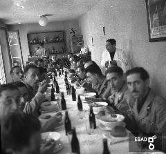 Miitari a mensa durante i pasti. [La foto è stata scattata nel 1940-1943 a SALERNO negli spazi di VIA BASTIONI dell'ex MONASTERO di SAN MICHELE ARCANGELO, di età longobarda e soppresso nel 1866; negli anni a cui risale la foto, una parte dell'ex Monastero era adibita a CASERMA della MILIZIA VOLONTARIA PER LA SICUREZZA NAZIONALE, indicata più semplicemente con l'acronimo MVSN, ma anche identificata con l'espressione CAMICIE NERE. In particolare la foto si riferisce alla visita in Caserma di un Console della MVSN. Su indicazione di Massimo La Rocca]