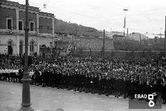 Persone ragazze e dirigenti di colonia nel piazzale davanti ad un edificio. [Foto scattata in Piazza Vittorio Veneto, sulla sinistra l'edificio è la stazione ferroviaria di Salerno. Nota a cura di Anna De Falco]