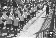 Bambini ed eeducatrici che camminano per una via cittadina. [La foto è stata scattata a Salerno nel 1937-1943 in via Porto. I bambini in corteo sono diretti verso l'odierna via Ligea allo Stabilimento balneare della colonia marina Mussolini. Una curiosità di questa foto è, a destra, sul marciapiede, l'ombra della recinsione che separava il molo 3 gennaio dal porto. Dal profilo dell'ombra si deduce che la recinzione era la stessa bella recinzione metallica, che ancora oggi si può ammirare e che fu realizzata nel ventennio fascista come si vede dal fascio littorio sagomato sulla superficie alla base di ogni pilastrino circolare e appuntito. Nota di Massimo della Rocca].