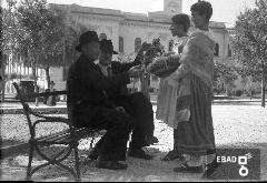 Bambine in abiti tradizionali che offrono prodotti alimentari a persone anziane sedute su una panchina in piazza F.Spirito in occasione della Festa dell'uva