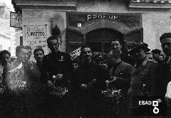 Militari con cestini d'uva davanti a un tabacchino. Festa dell'uva