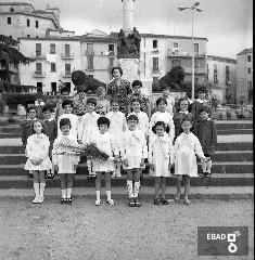 Scolaresca  con insegnante sulle scale del monumento ai caduti in piazza della Repubblica. [Maestra Maria Sparano. Su indicazione di Mariano Pastore]